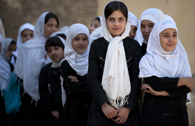 Kabul School girls wait for supplies handed out by NATO and Afghan forces. (Photo by G. A. Volb/Shutterjock)